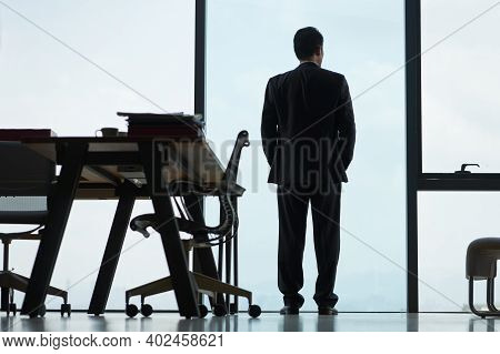 Rear View Of An Asian Corporate Executive Standing By The Window In Office Looking Out
