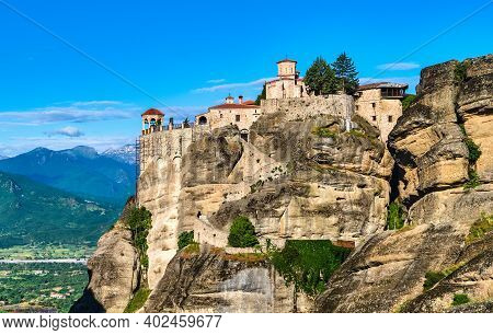 Close View Of Clifftop Varlaam Monastery And Rocky Slopes Of Meteora Valley Lit By Morning Sun. Vill