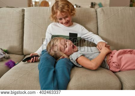 Adorable Little Siblings, Boy And Girl Having Fun, Playing Together While Watching Tv, Cuddling On A