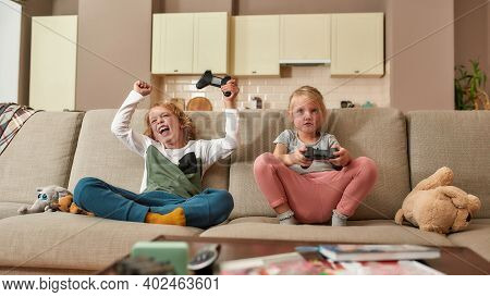 Two Cute Siblings, Little Boy And Girl Playing Video Games, Sitting On A Couch In The Living Room. C