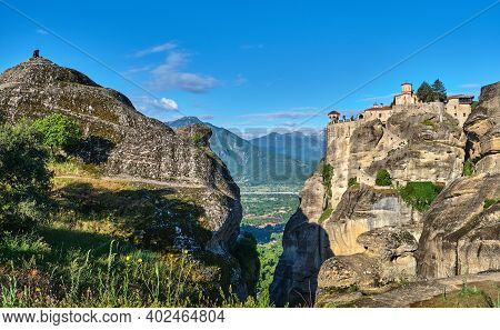 Morning View Of Varlaam Monastery And Rocks. Meteora Valley, Greece. Unrecognizable Adult Sitting On
