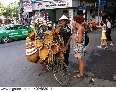 Hanoi, Vietnam, June 25, 2016: A Tourist Buys A Hat From A Man Who Sells Hats Loaded Onto A Bicycle