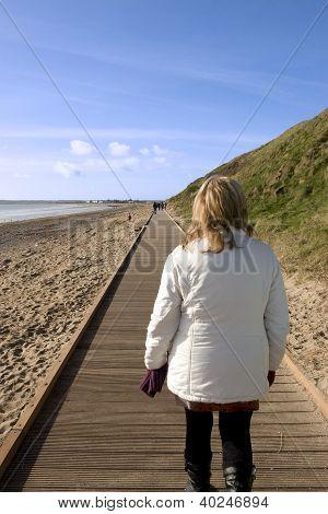 Woman Walking On Beach Boardwalk