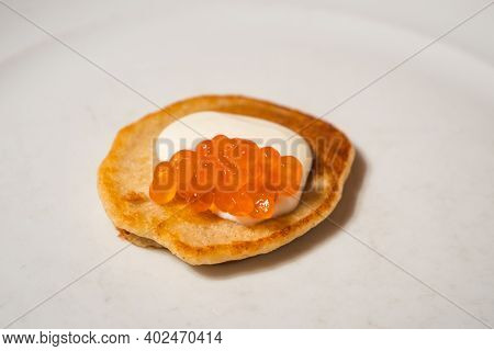 Single Red Salmon Caviar Blini With Sour Cream On A White Plate