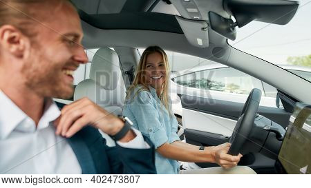 Selective Focus On Smiling Young Caucasian Woman Sitting On Driver Seat Beside Happy Young Man Insid