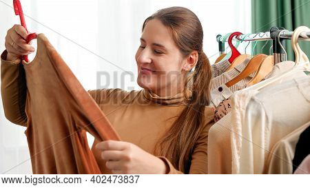 Smiling Young Woman Walking In Shopping Mall Or Boutique And Choosing Dress To Buy. Woman Doing Shop