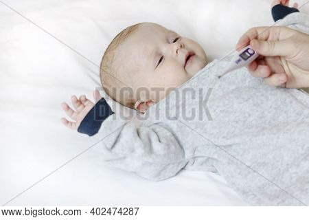 Mom Measures The Temperature Of A Sick, Sad Baby At Home. A Pediatrician Checks A Thermometer In A C