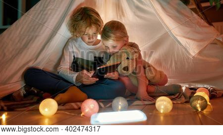 Adorable Little Children, Boy And Girl Using Digital Tablet While Spending Time Together, Sitting In