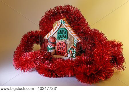 Gingerbread House With A Snowman In Red Tinsel On A Yellow Background