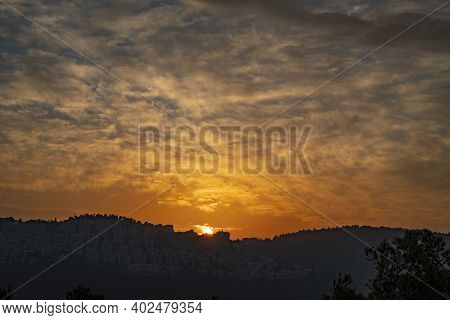 The Cloudy Sky Turns Golden As The Sun Rises On A Hazy Morning Over Jerusalem, Israel