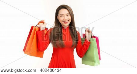 Positive Asian Girl In Vietnamese Ao Dai Dress Holding Shopping Bags While Standing Isolated On Whit