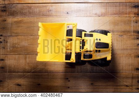 Toy Yellow Earthmover Toy On Wooden Background