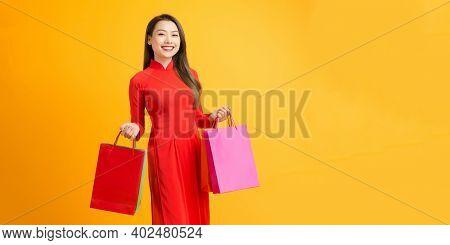 Cheerful Young Woman Wearing Ao Dai Dress Hold Shopping Bags