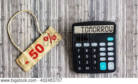 Marketing Concept: Sale 50 Off Written On Brown Tag And Wooden Table. The Calculator Displays The Wo
