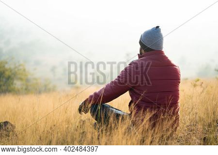 Back View Of Traveller Meditating On Top Of The Mountain During Cold Fogy Morning Sunrise - Concept