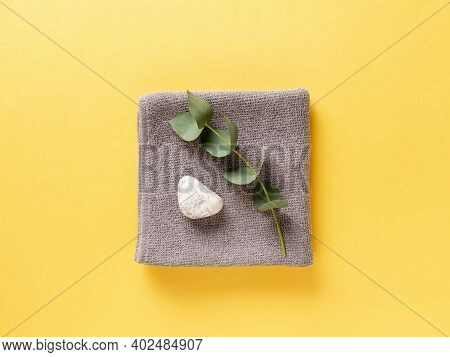 Spa Composition With Towel, Eucalyptus Branch And Zen Like Stone. Color Of The Year 2021. Illuminati