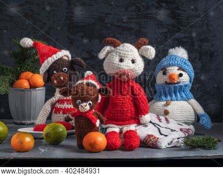 Handmade Crocheted Toys. A Snowman In A Blue Hat And Bulls In Red Caps