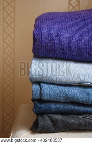 A Basic Wardrobe, Clothes Wardrobe. One-on-one Folded Jeans And A Purple Sweater On An Ottoman Close