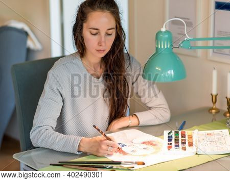 Woman Artist At Home In The Workshop Draws A Picture, Paint Brush Table And Lamp. Creation Of Creati