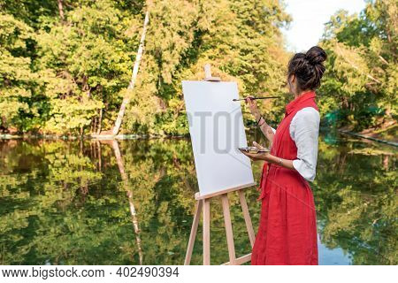 Free Space For Text, Woman Artist Summer Park Near Lake, River Pond, Draws A Picture, White Canvas.