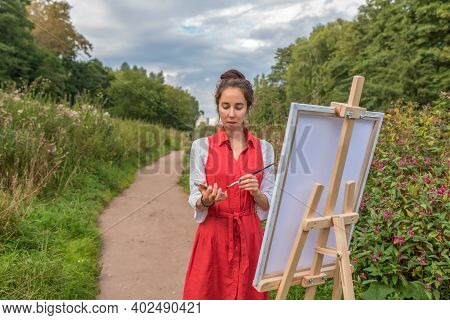 Path Into Distance Bushes Grass, Woman Artist In Summer In Park, Draws Picture. Free Space Copy Text