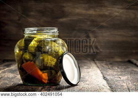 Marinated Cucumbers In Jar. On A Wooden Background.