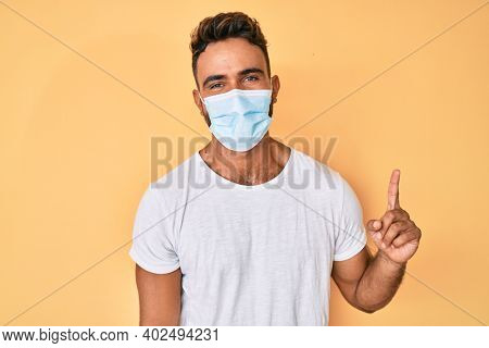 Young hispanic man wearing medical mask smiling with an idea or question pointing finger up with happy face, number one