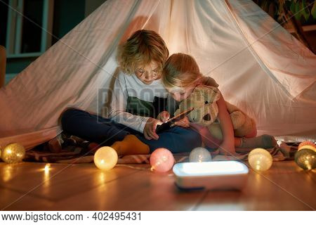 Two Little Siblings, Brother And Sister Looking Focused While Using Digital Tablet, Sitting In A Hut