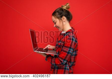 Side Profile Photo Of Pretty Youngwoman Holding Netbook Looking At Screen Typing On Keyboard Wearing
