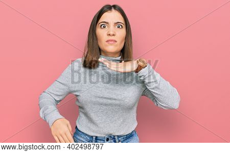 Young beautiful woman wearing casual turtleneck sweater cutting throat with hand as knife, threaten aggression with furious violence