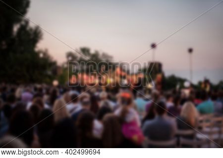 People Are Watching A Concert Of Classical Music. Blurred Young And Adult Women And Men And Other Pe
