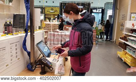 Russia, St. Petersburg 02.01.2021 Buyer In A Mask At A Self-checkout Counter During The Coronavirus