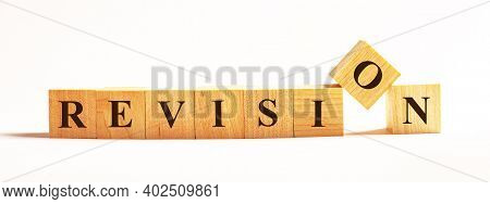 On A Light Background, Wooden Cubes With The Text Revision