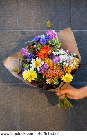 Beautiful Bouquet Of Seasonal Flowers. Hand With Bouquet Of Seasonal Flowers In Craft Paper. Bouquet