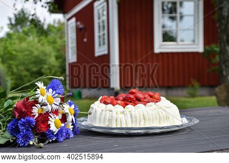 Flowers And A Cream Cake On A Garden Table With A Red House In The Background