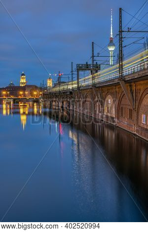 The River Spree, The Television Tower And A Moving Train In Berlin At Dusk