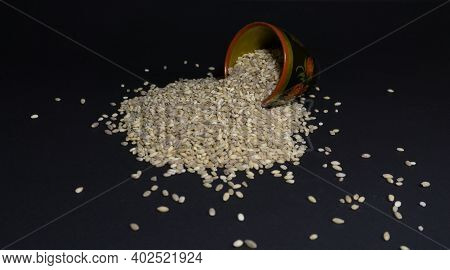 Raw Oatmeal In A Wooden Glass With Painting On A Black Background. Grains Of Pearl Barley Are Scatte