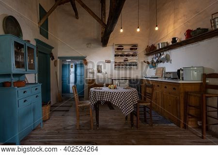 Traditional Interior Of Old Village Kitchen In Historic Country House With Stucco Walls, Wooden Beam