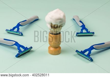 A Shaving Brush With Shaving Foam And Four Disposable Razors On A Blue Background. Set For Care Of A