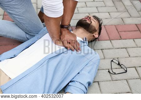 Passerby Performing Cpr On Unconscious Young Man Outdoors. First Aid