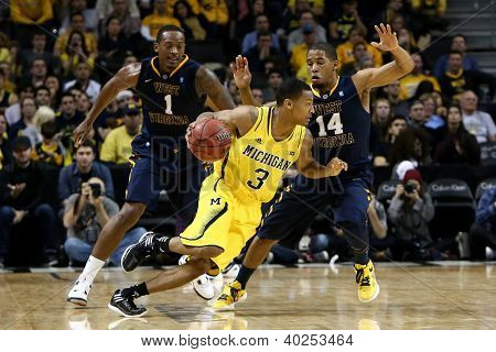 BROOKLYN-DEC 15: Michigan Wolverines guard Trey Burke (3) dribbles past West Virginia Mountaineers Dominique Rutledge (1) and Gary Browne (14) at Barclays Center on December 15, 2012 in Brooklyn.
