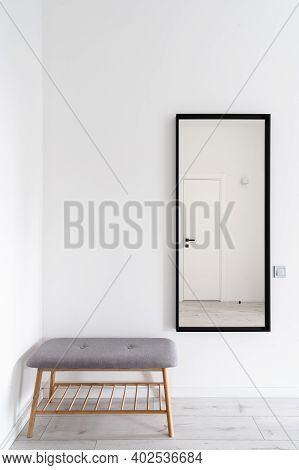 Vertical View Of Minimalist Hallway Interior With White Copy Space Wall, Monochrome Black Frame Mirr