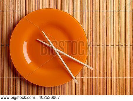 Plate And Chopsticks Top View. Wooden Chopsticks And Plate.