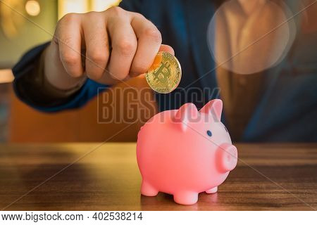 A Businessman's Hand Holds A Gold Cryptocurrency Bitcoin And Puts A Pig In A Piggy Bank. Bitcoin, Cr