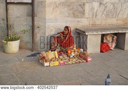 An Old Woman Sitting On Indian Street Market And Selling Colorful Bangles. Lady Selling Bangles On T