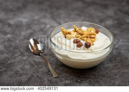 Bowl Of Yogurt With A Mix Of Nuts, Walnuts, Hazelnuts And Peanuts. Breakfast Cereal. Copy Space