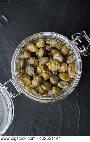 Baby Capers In Glas Jar, On Black Background, Top View