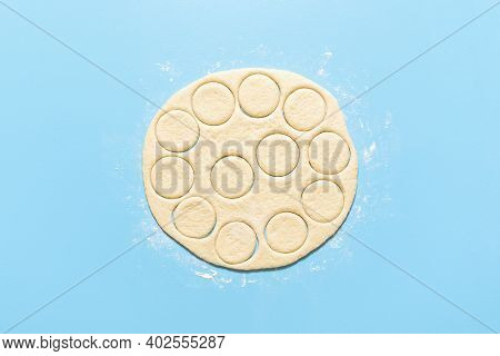 Cooking Doughnuts, Raw Donut Dough Cut In Round Shapes, On Blue Background. Flat Lay With Uncooked Y