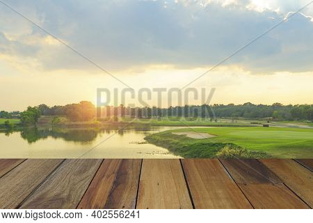 Wooden Floor And Golf Course Background. Fresh Spring Green Golf Course With Wood Floor. Beauty Natu