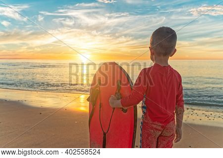 Cute Boy Holding Bodyboard Whilst Standing At The Beach And Watching Sunset At Chrieties Beach, Sout
